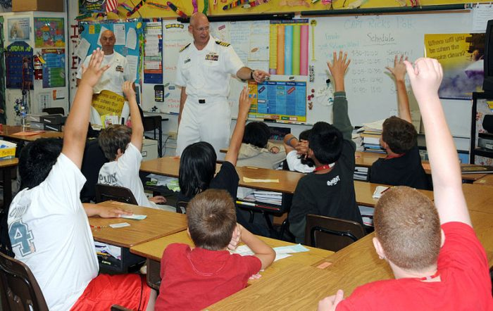 US Navy Capt. Ricks Polk, commanding officer of Afloat Training Group Middle Pacific answers questions from students during a Career Day at Iroquois Point Elementary School, courtesy Wikipedia Commons.