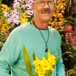 Bill Robson holding an Odontoglossum Yellow Parade orchid hybrid. Photo by Chuck Place.