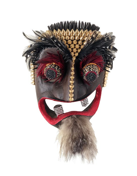 "Lynn Cunningham Brown, ""VaVaVaVoom,"" vintage Balinese hand-carved wood mask embellished with studs, Swarovski crystals, tacks, weasel fur, glitter, Chinese rooster and jungle cock feathers, 10x7x4 inches, on view at 10 West Gallery."